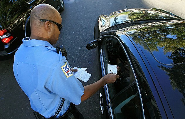 Police officer handing driver ticket
