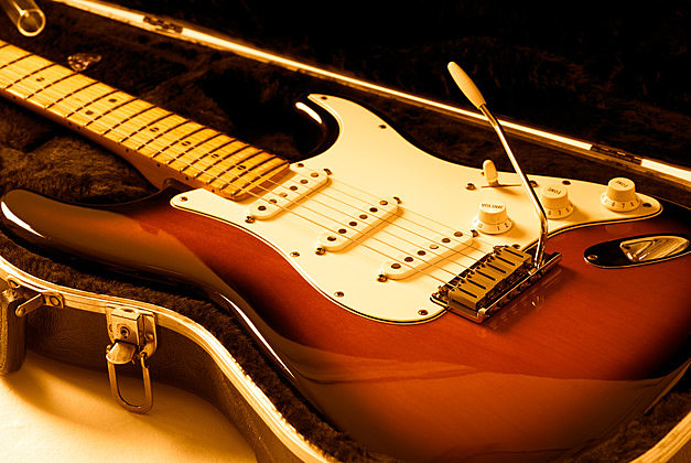 Electric guitar on case with orange lighting.